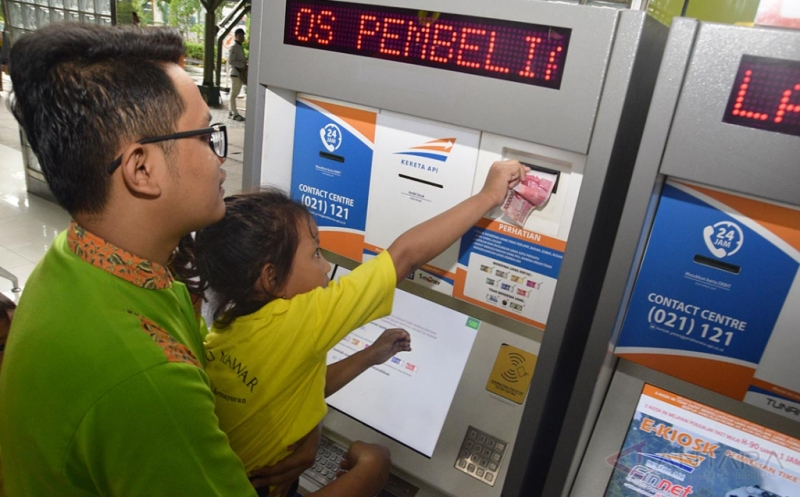 Seorang petugas membantu siswi Taman Kanak-Kanak (TK) membeli tiket dari mesin penjualan di Stasiun Gambir, Jakarta Pusat, Senin (20/3/2017). Kegiatan tersebut untuk mengkampanyekan transportasi umum khususnya Kereta Api kepada para generasi muda sejak usia dini.