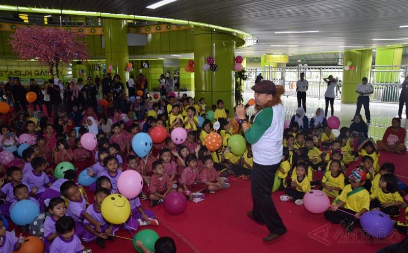 Pendongeng Ade M. Syafaat (kanan) bercerita tentang tentang peraturan-peraturan kerata api di di depan siswa-siswi Pendidikan Anak Usia Dini (PAUD) dan Taman Kanak-kanak (TK) di Stasiun Gambir, Jakarta Pusat, Senin (20/3/2017). Kegiatan tersebut dalam rangka memperingati Hari Dongeng Sedunia.