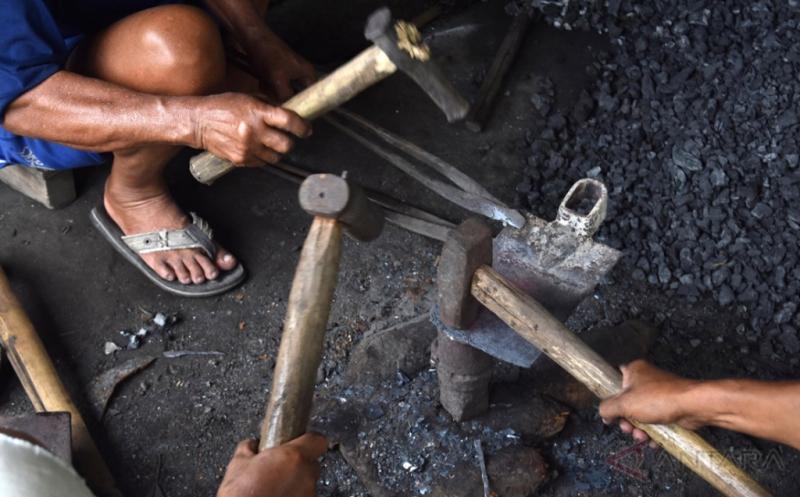 Sejumlah perajin memproduksi kerajinan alat pertanian cangkul di salah satu rumah produksi di Bokoharjo, Kabupaten Sleman, DI Yogyakarta, Senin (20/3/2017). Perajin setempat memproduksi sejumlah jenis alat pertanian, pertukangan, dan tambang, seperti cangkul, sabit, pisau, pedang, dan gergaji seharga Rp70.000-Rp100.000 per unit dan dipasarkan ke sejumlah daerah di DIY dan Klaten (Jawa Tengah).