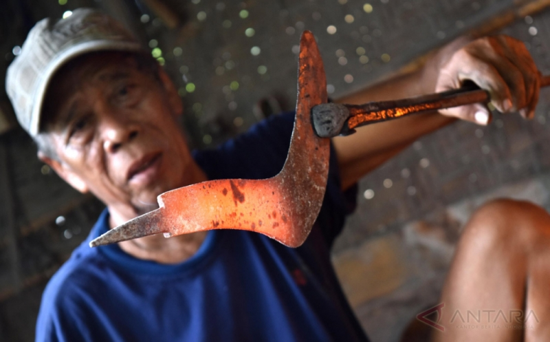 Seorang perajin memproduksi kerajinan alat pertanian sabit di salah satu rumah produksi di Bokoharjo, Kabupaten Sleman, DI Yogyakarta, Senin (20/3/2017). Perajin setempat memproduksi sejumlah jenis alat pertanian, pertukangan, dan tambang, seperti cangkul, sabit, pisau, pedang, dan gergaji seharga Rp70.000-Rp100.000 per unit dan dipasarkan ke sejumlah daerah di DIY dan Klaten (Jawa Tengah).