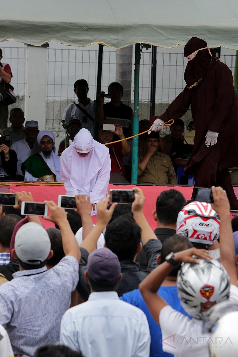 Terpidana menjalani hukum cambuk di halaman Masjid Baitul Mukminin, Desa Lamteh, Banda Aceh, Aceh, (20/3/2017). Mahkamah Syar'iah Kota Banda Aceh menvonis 12 terpidana pelanggar Peraturan Daerah (Qanun) Nomor 6/2014 tentang Ikhtilath (perbuatan bermesraan bukan dengan muhrimnya) dan qanun nomor 13/2003 tentang perjudian untuk penegakan hukum Syariat Islam yang telah berlaku di Provinsi Aceh.