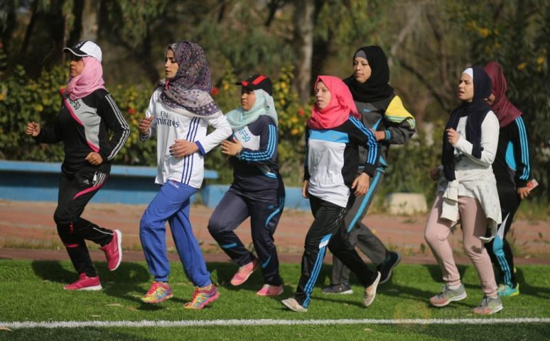 Sejumlah perempuan muslim Palestina berlari pada sesi latihan bisbol di Khan Youni, Palestina, Minggu (19/3/2017) waktu setempat. (REUTERS/Mohammed Salem)