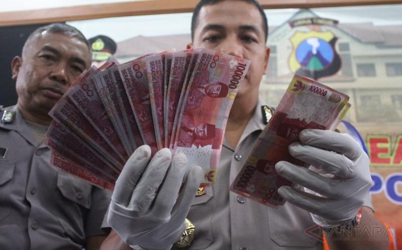 Polisi menunjukkan barang bukti yang disita dari tangan tersangka pengedar uang palsu di Polres Batu, Jawa Timur, Senin (20/3/2017). Dua orang komplotan pengedar uang palsu tersebut ditangkap bersama uang palsu pecahan 100 ribuan siap edar senilai jutaan rupiah.