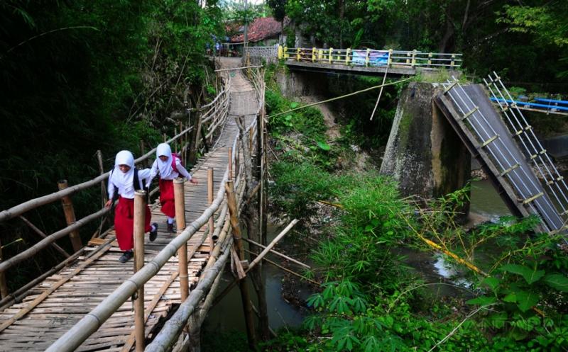 Sejumlah pelajar melewati jembatan darurat yang terbuat dari bambu di samping jembatan beton yang roboh di Desa Ngadipurwo, Blora, Jawa Tengah, Senin (20/3/2017). Meskipun berbahaya warga setempat terpaksa melewati jembatan darurat untuk beraktivitas karena Jembatan beton yang menghubungkan desa setempat roboh akibat tergerus arus sungai sejak Empat bulan yang lalu.
