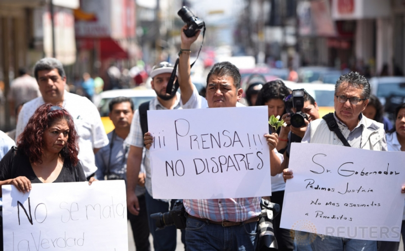 Sejumlah jurnalis menggelar unjuk rasa di Veracruz, Meksiko, Senin (20/3/2017) waktu setempat. Dalam aksinya para jurnalis mendesak pihak berwenang mengusut tuntas kematian rekan mereka, Ricardo Monlui Cabrera. Untuk diketahui, Ricardo Monlui ditembak mati saat meninggalkan sebuah restoran di Veracruz bersama istri dan anaknya. (REUTERS/Yahir Ceballos)