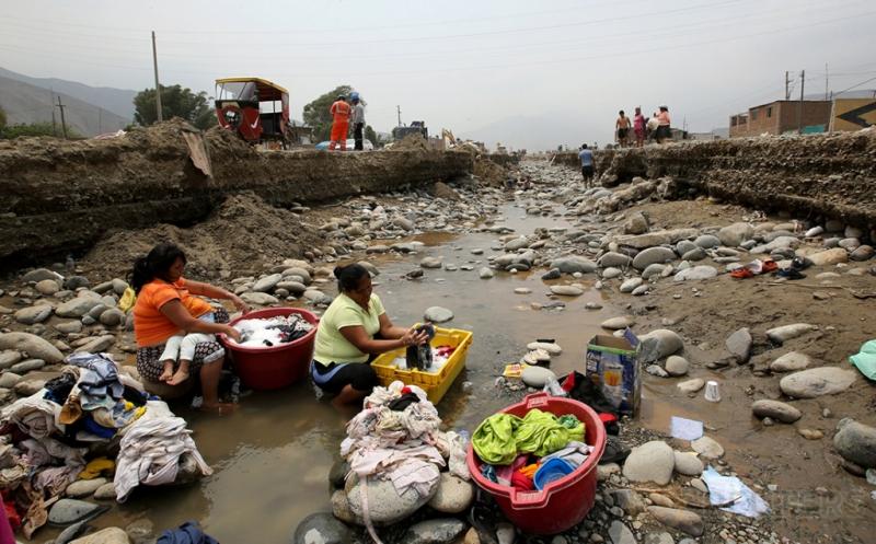 Sejumlah warga melakukan aktivitas mencuci pakaian di sungai pascabanjir bandang di Huachipa, Lima, Peru, Senin (20/3/2017). Sulitnya mendapatkan air bersih, membuat warga terpaksa mencuci pakainan di sungai ini. (REUTERS/Mariana Bazo)