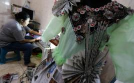 Perajin membuat busana dari bahan bekas di Surabaya, Jawa Timur, Selasa (21/3/2017). Busana yang dibuat dari bahan kertas koran, plastik kemasan, kantong plastik dan bahan bekas lainnya tersebut dijual berdasarkan pesanan dengan harga RP50.000 sampai Rp1.500.000 tergantung model dan tingkat kesulitannya.