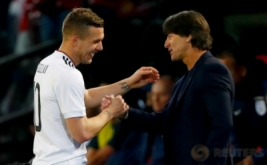 Lukas Podolski berjabat tangan dengan pelatih Jerman Joachim Low saat memasuki bangku cadangan pada laga persahabatan di Stadion Signal Iduna Park, Dortmund, Jerman pada Kamis (23/3/2017) dini hari WIB. Jerman sukses menaklukkan The Three Lions -julukan Inggris- dengan skor tipis 1-0. (Reuters / Wolfgang Rattay)