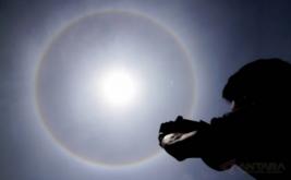 <p>  Warga mengabadikan fenomena Halo Matahari berbentuk cincin terlihat di atas langit Kota Lhokseumawe, Aceh, Kamis (30/3/2017).</p>