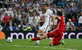 Cristiano Ronaldo (kiri) mencetak gol ke gawang Bayern Munich pada leg kedua perempatfinal di Santiago Bernabeu, Rabu (19/4/2017) dini hari WIB. (Reuters/Sergio Perez)