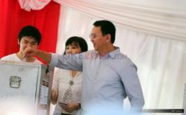 Calon Gubernur DKI Jakarta nomor urut dua Basuki Tjahaja Purnama (kanan) disaksikan istrinya Veronica Tan (tengah) dan putranya Nicholas Sean, memasukkan surat suara saat menyalurkan hak suaranya di TPS 54, kawasan Pantai Mutiara, Pluit, Penjaringan, Jakarta Utara, Rabu (19/4/2017). Pilkada DKI Jakarta putaran kedua diikuti dua pasang calon yaitu Ahok-Djarot dan Anies-Sandi.