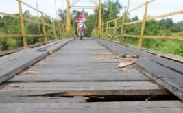 Warga melintas di atas jembatan gantung di Desa Simpang Peut, Kecamatan Arongan Lambalek, Aceh Barat, Aceh, Kamis (20/4/2017). Jembatan gantung penghubung antardesa yang dibangun sejak tahun 1993 tersebut sudah mulai rusak dan berlubang sehingga dapat membahayakan warga yang melintas.