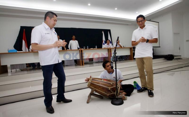Ketua Umum Partai Perindo Hary Tanoesoedibjo (kiri) bersama dengan Cawagub DKI Jakarta Sandiaga Uno  (kanan) menyaksikan peyandang disabilitas Yana memainkan alat musik gendang di DPP Partai Perindo, Jalan Diponegoro, Menteng, Jakarta Pusat, Kamis (20/4/2017). Partai Perindo menggelar syukuran keunggulan Anies-Sandi dari Ahok-Djarot, dalam hitung cepat semua lembaga survei terkait Pilkada DKI Jakarta putaran kedua.