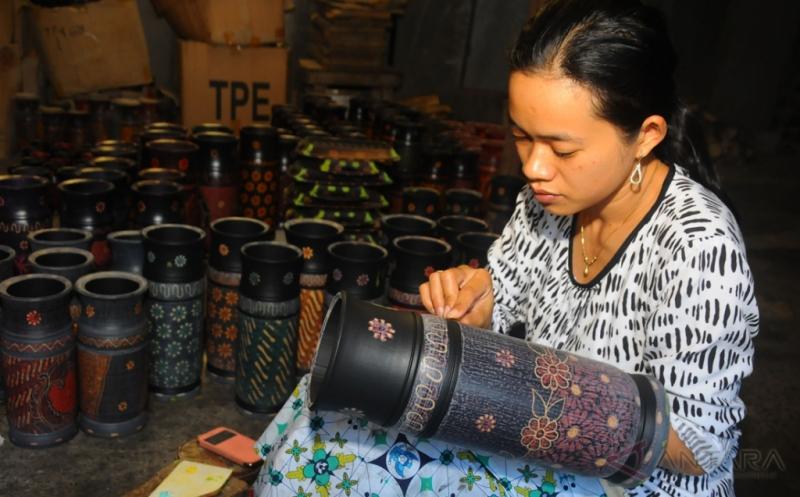 Seorang perajin menghaluskan permukaan bambu saat membuat kerajinan batik bambu di Ledok, Argomulyo, Salatiga, Jawa Tengah, Kamis (20/4/2017). Berbagai jenis hasil kerajinan berbahan dasar bambu betung yang diolah menjadi tudung saji, tempat pensil, vas bunga, nampan, dan gelang tersebut telah dijual ke Yogyakarta, Solo, Jakarta, dan Bali dengan harga Rp10 ribu hingga Rp95 ribu, tergantung jenis dan ukuran.