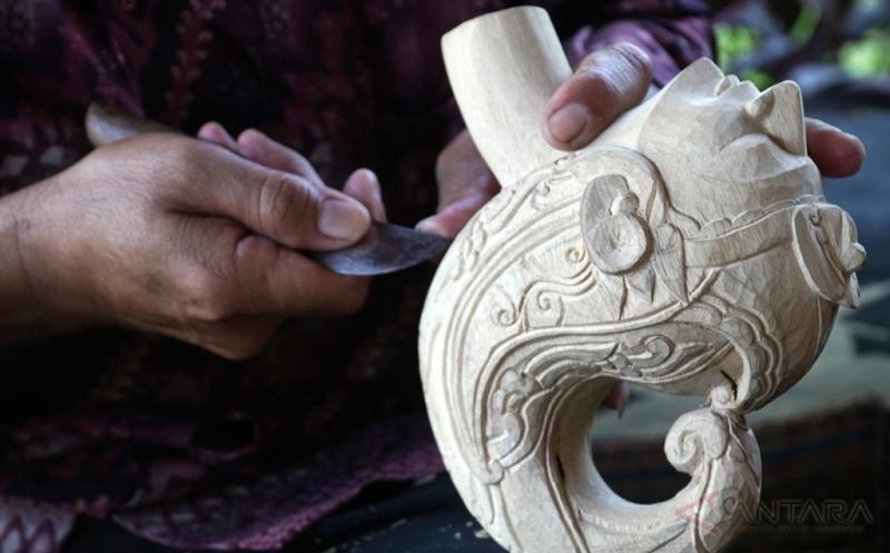 Perajin Wayang Golek, Jani, membuat ukiran mahkota pada wayang, di Kabupaten Purwakarta, Jawa Barat, Kamis (20/4/2017). Selain untuk kepentingan cenderamata, Jani juga membuat wayang sebagai upaya untuk menjaga kelestarian Wayang Golek Sunda.