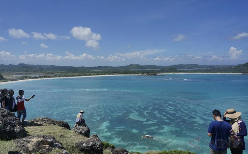 Wisatawan berada di kawasan wisata Bukit Merese, Lombok Tengah, Nusa Tenggara Barat, Kamis (20/4/2017). Bukit Merese yang menawarkan pesona perbukitan dan panorama pantai dari ketinggian itu menjadi daya tarik tersendiri bagi para wisatawan yang berkunjung ke Lombok Tengah.