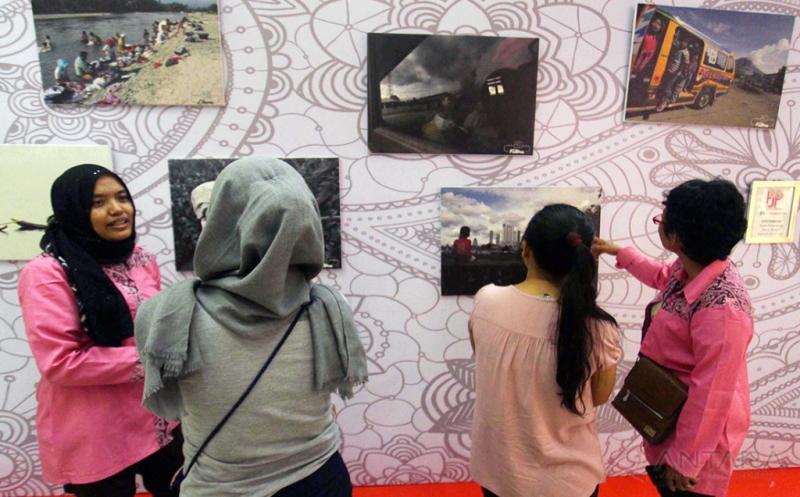 Dua orang jurnalis menjelaskan kepada pengunjung mengenai foto yang dipamerkan di Medan, Sumatera Utara, Kamis (20/4/2017). Dalam menyambut Hari Kartini para jurnalis perempuan di Medan yang tergabung dalam Forum Jurnalis Perempuan (FJP) Indonesia menggelar pameran foto yang menceritakan tentang aktivitas perempuan.