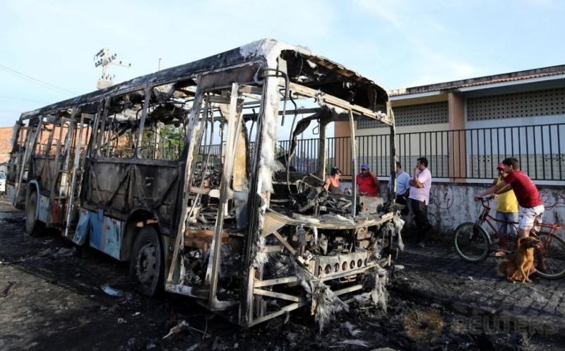 Sejumlah warga melihat bangkai bus yang ludes terbakar di Fortaleza, Brasil, Kamis (20/4/2017) waktu setempat. Sekira 20 bus dibakar dalam dua hari terakhir, diduga merupakan aksi balasan dari pemindahan tahanan di penjara Fortaleza. (REUTERS/Paulo Whitaker)