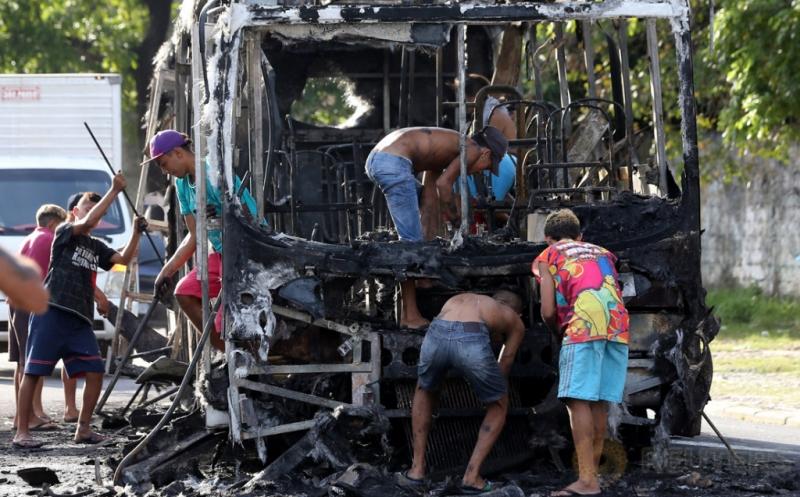Sejumlah warga berada di bangkai bus yang ludes terbakar di Fortaleza, Brasil, Kamis (20/4/2017) waktu setempat. Sekira 20 bus dibakar dalam dua hari terakhir, diduga merupakan aksi balasan dari pemindahan tahanan di penjara Fortaleza. (REUTERS/Paulo Whitaker)