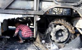 Seorang warga berada di kolong bangkai bus yang ludes terbakar di Fortaleza, Brasil, Kamis (20/4/2017) waktu setempat. Sekira 20 bus dibakar dalam dua hari terakhir, diduga merupakan aksi balasan dari pemindahan tahanan di penjara Fortaleza. (REUTERS/Paulo Whitaker)