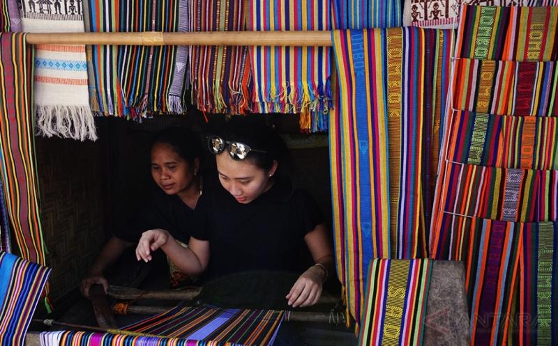 Pegunjung mencoba menenun di kawasan wisata Desa Sade, Pujut, Lombok Tengah, Nusa Tenggara Barat, Kamis (20/4/2017). Desa yang masih kuat menjaga tradisi Suku Sasak (suku asli Pulau Lombok) itu menjadi salah satu destinasi wisata seni dan budaya andalan di Lombok Tengah.