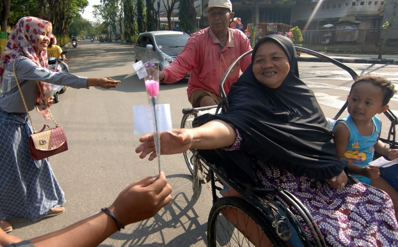 Aktivis HMI membagikan bunga kepada pengguna jalan raya di Pamekasan, Jawa Timur, Jumat (21/4/2017). Pembagian bunga tersebut dalam rangka memperingati Hari Kartini.