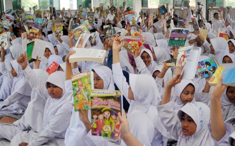 Sejumlah siswa menunjukkan buku saat membaca buku bersama di SD Insan Kamil, jalan raya Dramaga, Bogor, Jawa Barat, Jum'at (21/3/2017). Kegiatan membaca buku bersama yang diikuti 400 siswa tersebut selain untuk memperingati Hari Kartini juga bertujuan menumbuhkan dan meningkatkan minat baca di kalangan siswa.