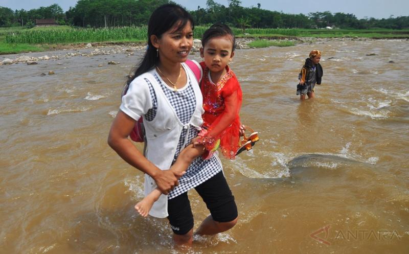 Sejumlah wanita menggendong putri mereka yang akan mengikuti perayaan Hari Kartini menyeberangi Sungai Blukar di Dusun Cipluk, Sidokumpul, Patean, Kendal, Jawa Tengah, Jumat (21/4/2017). Meski harus menerjang arus sungai yang cukup deras karena tidak tersedianya jembatan, puluhan pelajar di dusun itu tetap bersemangat berangkat sekolah untuk mengikuti upacara peringatan Hari Kartini.