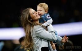 Istri Pablo Zabaleta menggendong anaknya usai Manchester City melumat West Bromwich Albion 3-1 di Etihad Stadium, Rabu (17/5/2017) dini hari WIB. Laga tersebut merupakan partai kandang pamungkasnya bersama Manchester City. (Reuters/Andrew Yates)