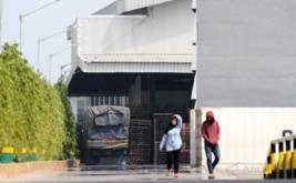 Pekerja melintas di dekat sebuah mobil truk bermuatan bawang putih yang terpasang garis polisi, di gudang PT Tunas Perkasa Indonesia, di kawasan Tarumajaya, Bekasi, Jawa Barat, Rabu (17/5/2017). Bareskrim Mabes Polri melakukan penggerebekan di gudang perusahaan tersebut karena menimbun 182 ton bawang putih yang diduga berasal dari China dan India yang tidak dilengkapi dengan dokumen impor yang lengkap.