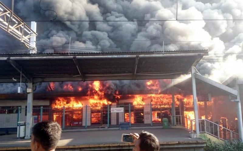 Seorang warga mengabadikan kebakaran yang terjadi di Stasiun Klender, Jatinegara, Jakarta Timur, Jumat (19/5/2017). Sebanyak sembilan unit mobil pemadam kebakaran dikerahkan ke lokasi untuk memadamkan api.