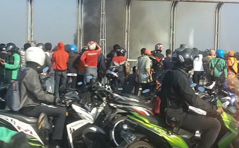 Puluhan pengendara sepeda motor menyaksikan kebakaran yang terjadi di Stasiun Klender, Jatinegara, Jakarta Timur, Jumat (19/5/2017). Banyaknya pengendara yang berhenti untuk menyaksikan kebakaran mengakibatkan lalu lintas di lokasi menjadi padat.