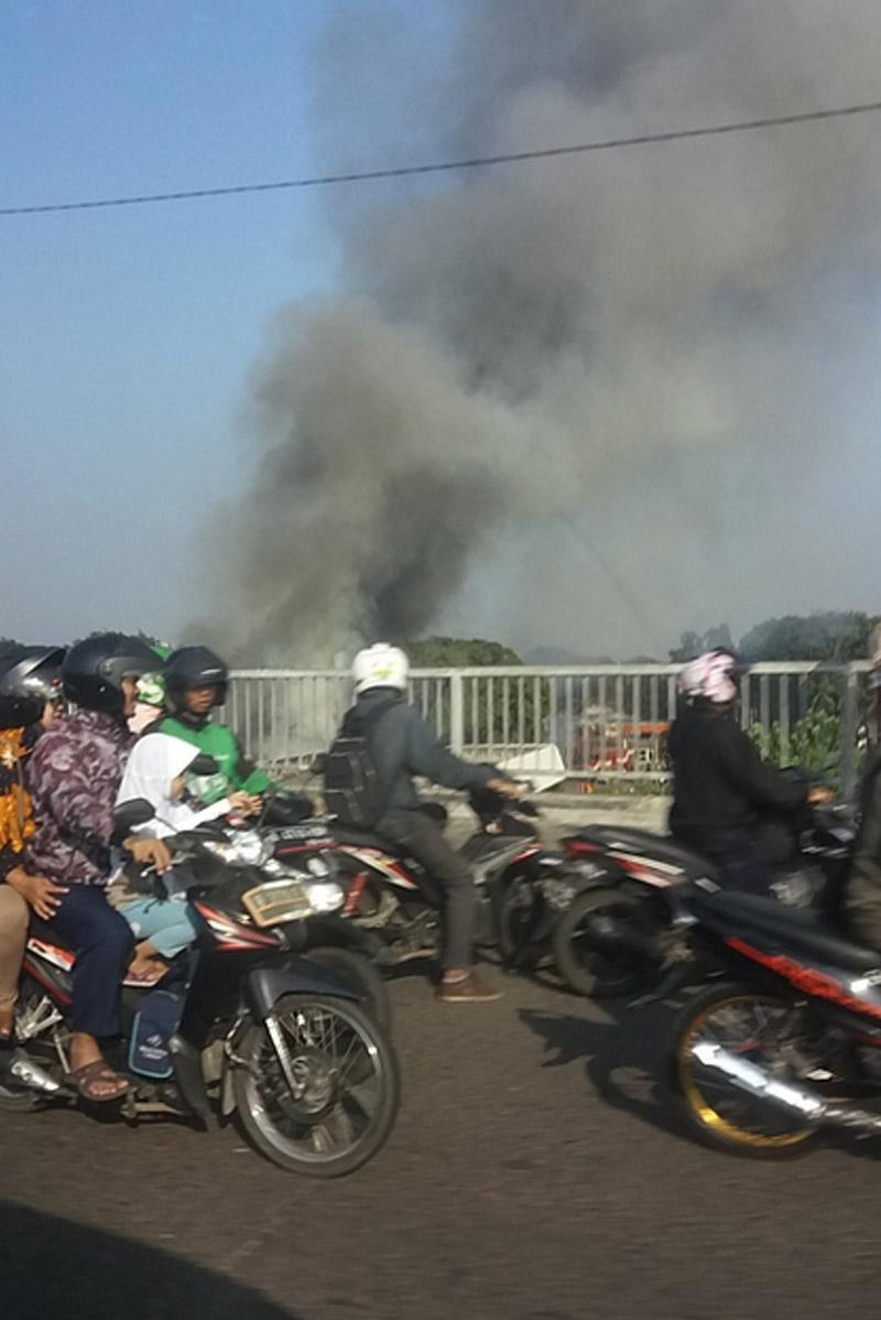 Sejumlah pengendara sepeda motor menyaksikan kebakaran yang terjadi di Stasiun Klender, Jatinegara, Jakarta Timur, Jumat (19/5/2017). Banyaknya pengendara yang berhenti untuk menyaksikan kebakaran mengakibatkan lalu lintas di lokasi menjadi padat.
