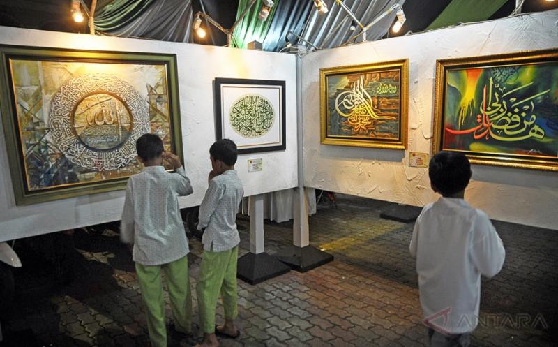 Pengunjung memperhatikan karya seni Kaligrafi saat pameran kaligrafi Islam di komplek Masjid Agung Kudus, Jawa Tengah, Kamis (18/5/2017). Pameran yang diadakan Asosiasi Kaligrafi Arab yang berlangsung 16-25 Mei 2017 tersebut untuk mengenalkan serta mengangkat potensi seni kaligrafi Arab kepada masyarakat umum.
