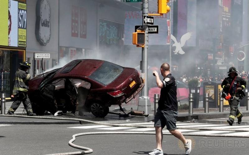 Petugas pemadam kebakaran menyemprotkan air pada sebuah mobil yang mengalami kecelakaan di Times Square, New York, Amerika Serikat, Kamis (18/5/2017) waktu setempat. Satu orang tewas dan 22 lainnya terluka akibat mobil berkecepatan tinggi menabrak pejalan kaki di lokasi ini. (REUTERS/Mike Segar)