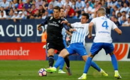 Luis Hernandez (tengah) berusaha merebut bola dari Cristiano Ronaldo di Estadio La Rosaleda, Senin (22/5/2017) dini hari WIB. (Reuters/Juan Medina)