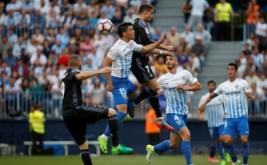 Cristiano Ronaldo (atas) memenangi duel udara dengan Federico Ricca di Estadio La Rosaleda, Senin (22/5/2017) dini hari WIB. (Reuters/Jon Nazca)