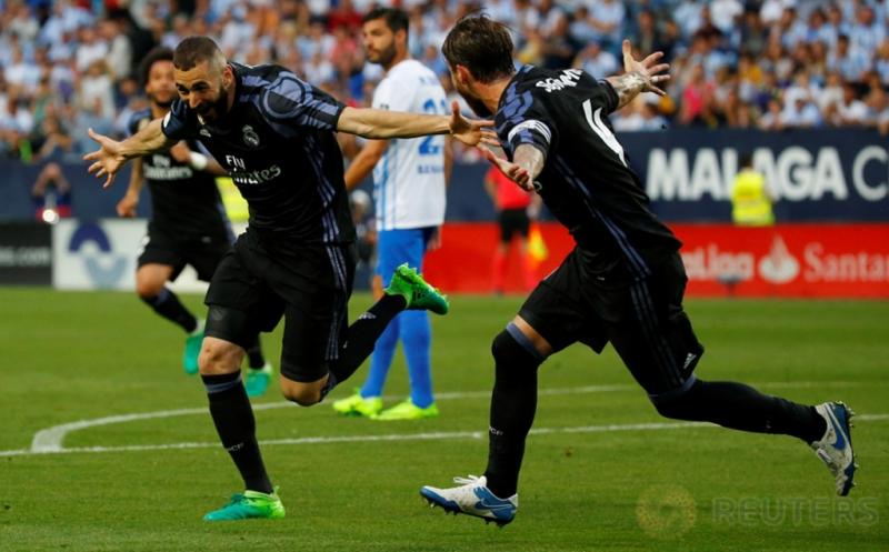 Karim Benzema (kiri) selebrasi usai mencetak gol ke gawang Malaga di Estadio La Rosaleda, Senin (22/5/2017) dini hari WIB. Memanfaatkan bola rebound hasil sundulan Sergio Ramos, Benzema melepaskan sepakan yang meluncur deras ke dalam gawang Malaga. (Reuters/Juan Medina)