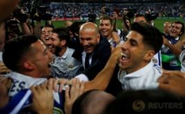 Para pemain Real Madrid memeluk pelatih mereka, Zinedine Zidane usai Madrid mengalahkan dua gol tanpa balas di Estadio La Rosaleda, Senin (22/5/2017) dini hari WIB. Kemenangan tersebut juga memastikan Real Madrid sebagai jawara Liga Spanyol 2016-2017. (Reuters/Jon Nazca)
