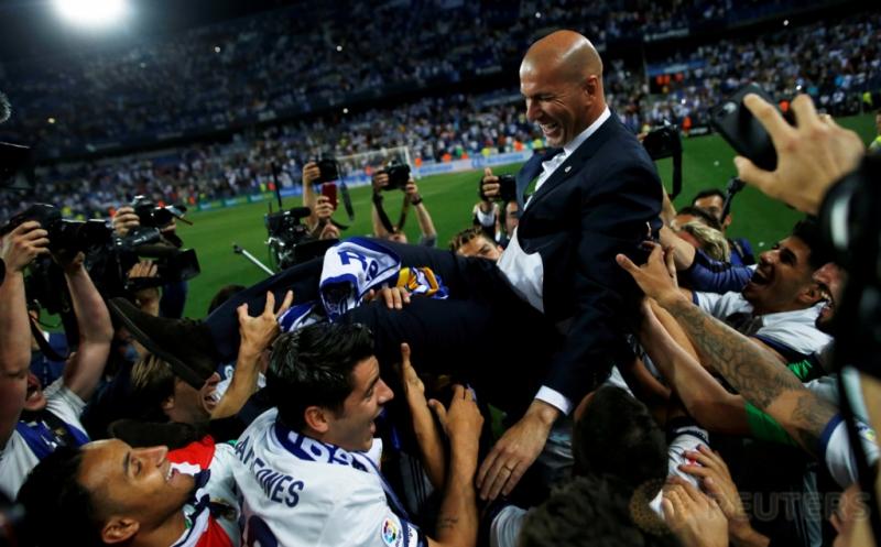 Pemain Real Madrid mengangkat pelatih mereka, Zinedine Zidane usai Madrid mengalahkan dua gol tanpa balas di Estadio La Rosaleda, Senin (22/5/2017) dini hari WIB. Kemenangan tersebut juga memastikan Real Madrid sebagai jawara Liga Spanyol 2016-2017. (Reuters/Jon Nazca)