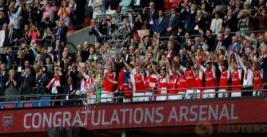 Laurent Koscielny dan Per Mertesacker mengangkat trophy dan selebrasi bersama tim saat meraih juara FA Cup 2017 usai mengalahkan Chelsea dengan skor 2-1 di Wembley Stadium, Minggu (28/5/2017) dini hari WIB. Reuters / Andrew Yates