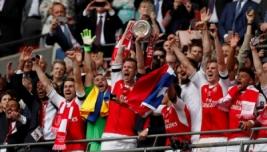 Laurent Koscielny dan Per Mertesacker mengangkat trophy dan selebrasi bersama tim saat meraih juara FA Cup 2017 usai mengalahkan Chelsea dengan skor 2-1 di Wembley Stadium, Minggu (28/5/2017) dini hari WIB. Reuters / John Sibley
