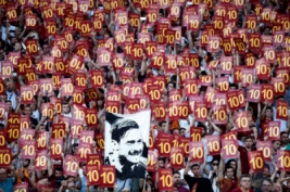 Supporter Roma mengangkat spanduk bernomor 10 untuk Francesco Totti pada laga terakhirnya untuk As Roma di Stadion Olimpico Roma Minggu (28/5/2017). Francesco Totti Menyudahi karirnya bersama As Roma selama 25 Musim.Reuters / Stefano Rellandini