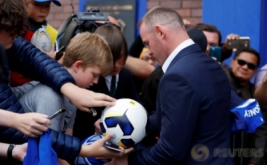 Wayne Rooney membubuhkan tandatangan pada bola penggemarnya usai konferensi pers di Liverpool, Inggris, Senin (10/7/2017) waktu setempat. Rooney memilih kembali ke klub masa kecilnya Everton, setelah 13 tahun terakhir membela Manchester United. (REUTERS/Phil Noble)